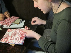 Kayla stitches the binding of her book